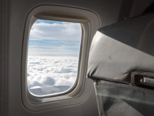 Cloudy sky seen through the window of an airplane