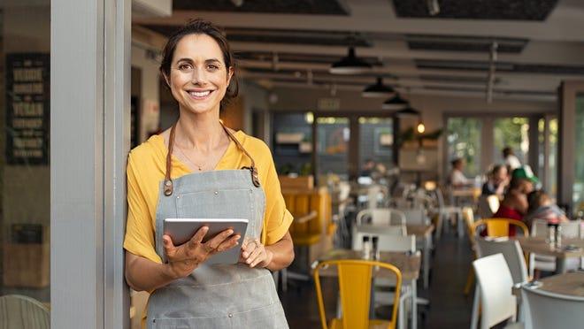 Smiling hostess at restaurant entrance