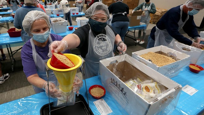 Laurie Boelk, left, holds a bag up to the funnel as Kristi Hartley reaches over to pour textured soybean flour in during The Outreach Program event where volunteers packaged 50,000 meals on Saturday, Oct. 17, 2020.