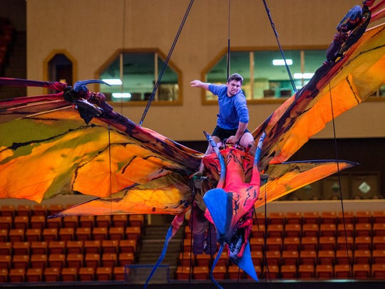 A cast member rides atop a flying Toruk puppet during