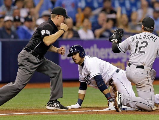 Third base umpire Cory Blaser, left, calls Tampa Bay Rays' Yunel Escobar out after being tagged by Chicago White Sox third baseman Conor Gillaspie, right, after trying to go from first to third on a single by Rays James Loney during the fourth inning of a baseball game Friday, Sept. 19, 2014, in St. Petersburg, Fla. (AP Photo/Chris O'Meara)