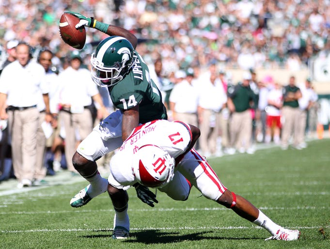 Oct 12, 2013; East Lansing, MI, USA; Michigan State Spartans wide receiver Tony Lippett (14) is tackled by Indiana Hoosiers cornerback Michael Hunter (17) during the first half in a game at Spartan Stadium. Mandatory Credit: Mike Carter-USA TODAY Sports