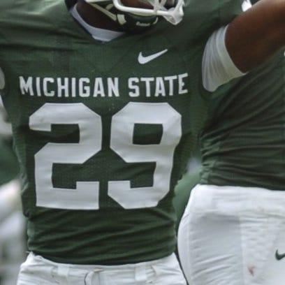 MSU's Chris Rucker (29) signals a Spartan's possession