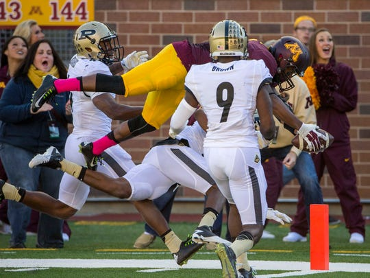 Oct 18, 2014; Minneapolis, MN, USA; Minnesota Golden Gophers wide receiver KJ Maye (1) dives for a touchdown against Purdue Boilermakers defensive back Frankie Williams (24) and defensive back Anthony Brown (9) in the second half at TCF Bank Stadium. The Gophers won 39-38. Mandatory Credit: Jesse Johnson-USA TODAY Sports