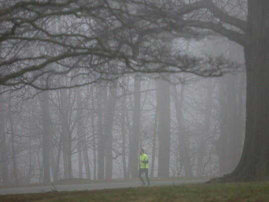 A runner makes his way through Rockford Park in the early morning fog.