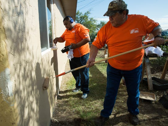 Estevan Silva, left, and Gave Espinoza, right, volunteers from Home Depot, painting the front of Frances Madrid's home Thursday November 9, 2017. The group of volunteers helping renovate Madrid's home are part of a program that go out and help veterans and their families.