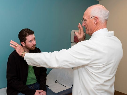 Dr. Stephen Gardner of Southeastern Neurosurgical and Spine Institute examines Clark McAlister who is recovering from a near-fatal motorcycle crash.