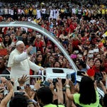 Pope Francis waves as he arrives at the University of Santo Tomas during his visit to Manila on January 18, 2015.