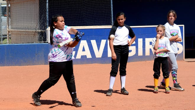 Reigna Hernandez, 13, makes contact at the plate during the Cavegirls softball hitting clinic on Tuesday.