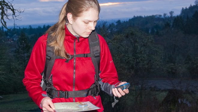 Anne Marie Collum, the daughter of Steve Dougherty, the instructor of the annual Chemeketans Route Finding School, checks her bearings using all of the skills taught during the school: map, compass and GPS.