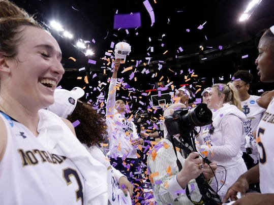 Notre Dame forward Brianna Turner, back center, uses a hat to throw up confetti after her team defeated Oregon 84-74 in a regional final at the NCAA women's college basketball tournament, Monday, March 26, 2018, Spokane, Wash. (AP Photo/Young Kwak)