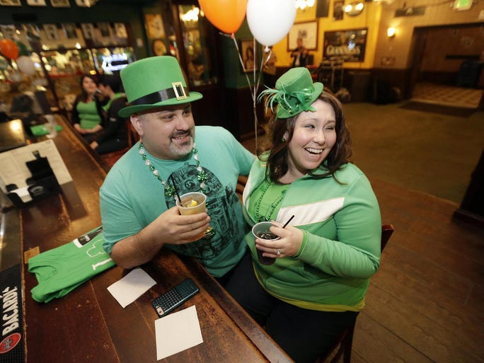 Matt Bieganski and his wife, Kristal, of Oak Creek are decked out in green while celebrating St. Patrick's Day at Mo's Irish Pub on W. Wisconsin Ave. in downtown Milwaukee. People hit the area bars as early as 6 a.m. in Milwaukee to celebrate St. Patrick's Day.
