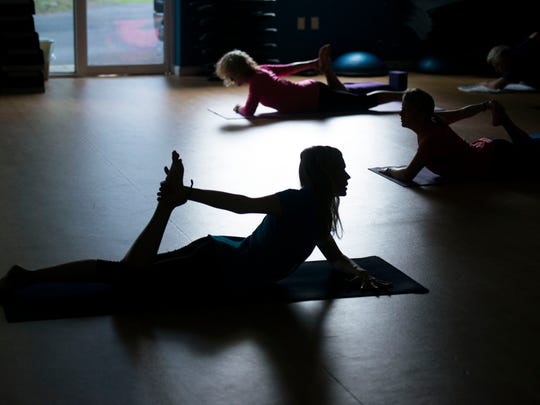 Lora Cole, center, of Yoga at the Beach teaches a class