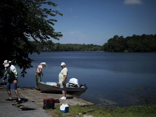Three fishermen from Lewes pack up after a morning on Wagamon Pond.