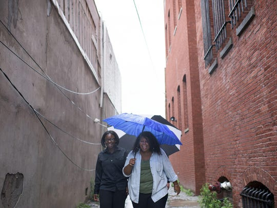 Students Aisha Dorley, 20, left, and Timnit Kefela, 23, brave the rain to study their plantings outside Wednesday morning in Camden.