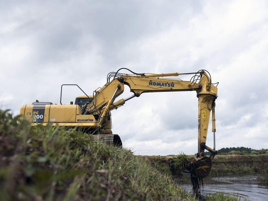An excavator cleans up a waterway at Pine Island Cranberry in Chatsworth.