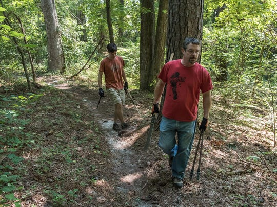 Mike Perry of Delmar and his son, Chris, walk toward an area of overgrowth carrying machetes and other gardening tools on a trail near North Park Drive.
