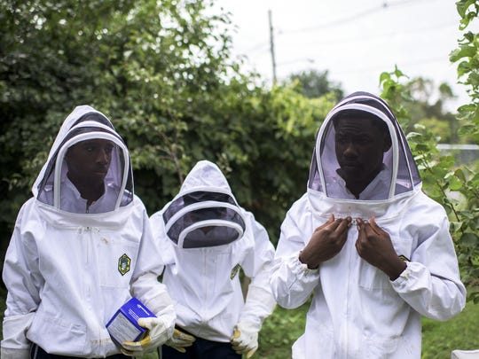 Eco interns Marquise Young, 15, from left, Alex Rosario, 16, and assistant farmer Dimitrius Eliza, 17, suit up to handle a beehive at the Ferry Ave Orchard Wednesday, August 19 in Camden.