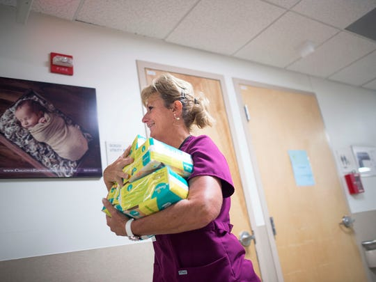 Certified nursing assistant Vicky Mallet carries a stack of baby diapers inside the Women's Health Pavilion at Beebe Healthcare  in Lewes.