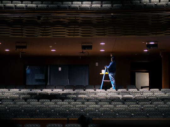 Painter Eddie Fleetwood touches up a ceiling inside the new performing arts center auditorium inside the Roland E. Powell Convention Center in Ocean City.