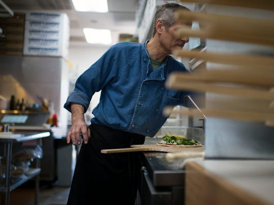 Owner and pizza chef Ira Mensh tops a personal pizza