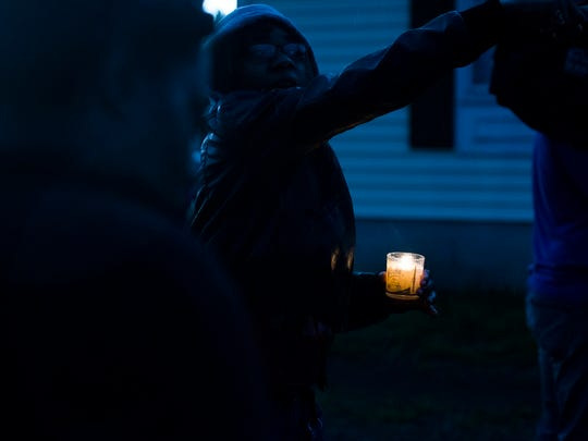 A woman holds a candle as it begins to rain at a prayer vigil for the Todd family Friday evening.