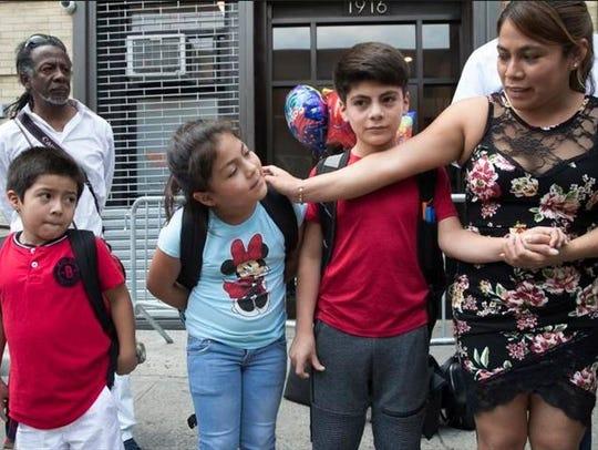 Yeni Gonzalez Garcia, right, stands with her children