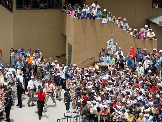 Tiger Woods walks to the first tee during the final