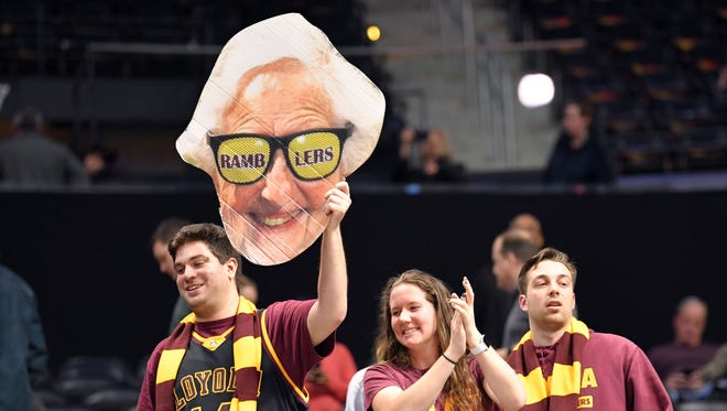 A Loyola Ramblers fans hold up a cutout of team chaplain Sister Jean during an Elite Eight game.