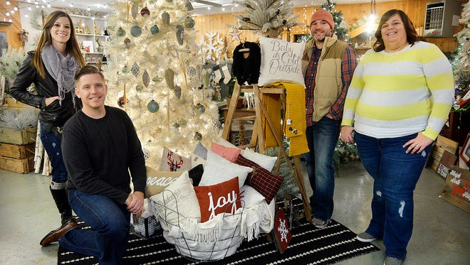 Copper Pony owners Brandon Johnson, left, and Josh Hoffman are pictured with two of their most prominent artists, Jenna Schaefer, far left, and Megan Rauch on Tuesday night, Nov. 10. Copper Pony is a business that blends repurposed items, crafts and vintage good based in rural Clearwater. They are prepping for the first of their holiday events of this season.