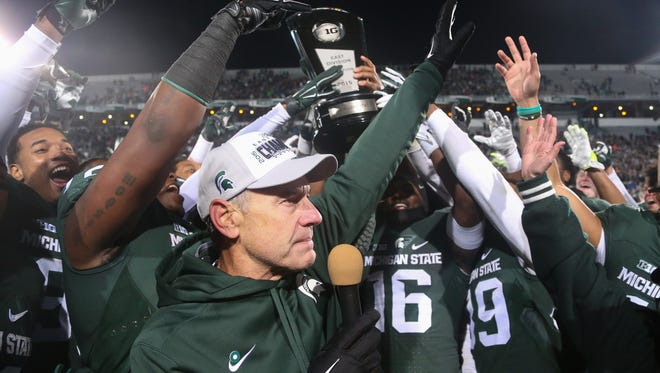 Michigan State coach Mark Dantonio talks to fans after his team received the East Division championship trophy after beating the Penn State Nittany Lions, 55-16, on Nov. 28.