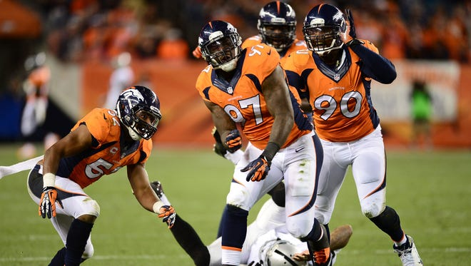 Denver Broncos defensive end Malik Jackson (97) reacts to his sack of Oakland Raiders quarterback Terrelle Pryor (2) with and outside linebacker Wesley Woodyard (52) and outside linebacker Shaun Phillips (90) late in the second quarter at Sports Authority Field at Mile High.