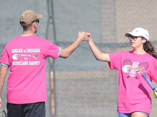 Cooper senior Liana Burris, right, celebrates a point with teammate Aaron Langham, a Cooper grad now with the  Abilene Police Department, during their match against Abilene High senior Luke Phillips and Abilene firefighter Justin Riley. Both teams were playing in the AHS-Cooper fundraiser for Hurricane Harvey relief Saturday, Jan. 27, 2018 at Rose Park Tennis Center.