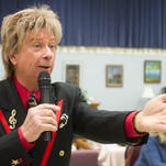 In a show at the Hartland Senior Center, Barry Manilow tribute artist Frank Sternett sings a medley of popular songs, highlighting some of Manilow's big hits. He moved from person to person in the audience, stopping here with Mary Lynn Thompson.