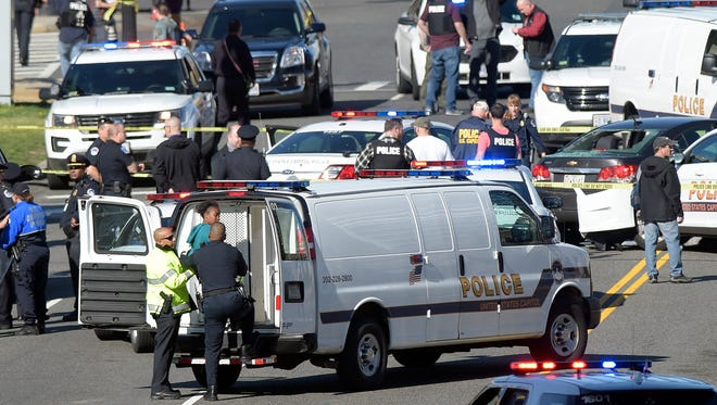 A woman, center, is taken into custody on Capitol Hill in Washington, Wednesday, March 29, 2017. Police say a driver struck a U.S. Capitol Police cruiser near the U.S. Capitol and was taken into custody. (AP Photo/Susan Walsh)