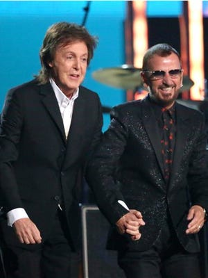 FILE - In this Jan. 26, 2014 file photo, Paul McCartney, left, and Ringo Starr appear at the 56th annual Grammy Awards in Los Angeles. McCartney will induct his former Beatle mate, Ringo Starr, into the Rock and Roll Hall of Fame next month. The 30th annual induction ceremony is scheduled for Cleveland's Public Hall on April 18. (Photo by Matt Sayles/Invision/AP, File)