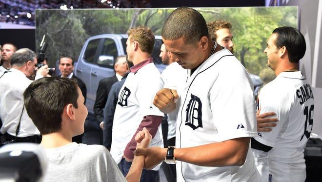 Tigers' Victor Martinez shows Zach Latimer, 12, of Farmington a new handshake.