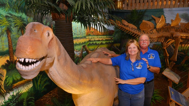 Steve and Donna Cayer, ownersof the Dinosaur Store in Cocoa Beach, are opening the up the Museum of Dinosaurs and Ancient Cultures.  The not-for-profit museum opens Saturday, Earth Day. They are standing by a life size replica of a Camarasaurus.