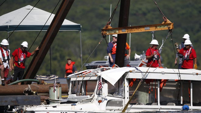 In this July 23, 2018, photo, a duck boat that sank in Table Rock Lake in Branson, Mo., is raised after it went down the evening of July 19 after a thunderstorm generated near-hurricane strength winds, killing 17 people.