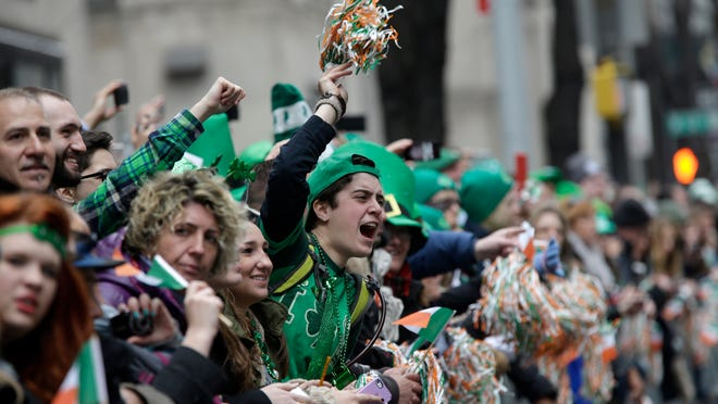 People wave at the participants marching up Fifth Avenue during Tuesday's St. Patrick's Day Parade in New York City.