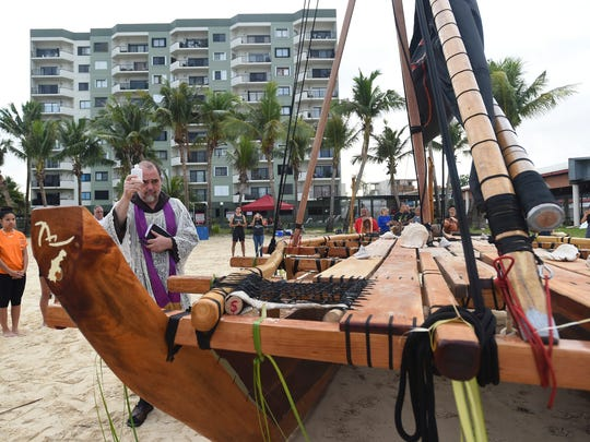 Father Eric Forbes blesses Ta Ina, Guam's first double-hull canoe in more than 400 years, at Dungca's Beach in Tamuning on Feb. 10, 2018.