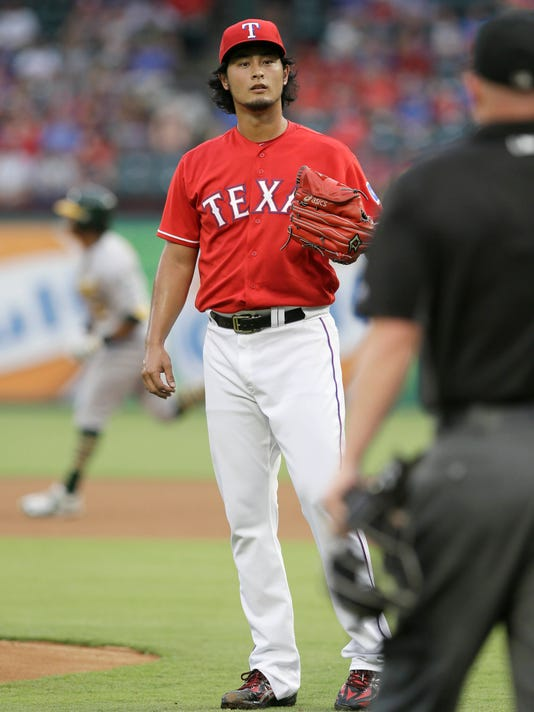 Texas Rangers starting pitcher Yu Darvish waits for a new ball as Oakland Athletics' Khris Davis runs out his solo home run during the first inning of a baseball game in Arlington, Texas, Wednesday, July 27, 2016. (AP Photo/LM Otero)