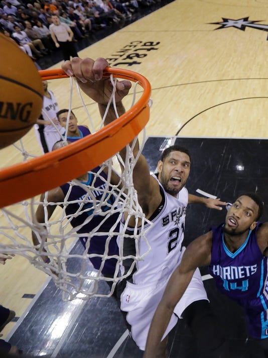 San Antonio Spurs' Tim Duncan (21) goes to the basket over Charlotte Hornets' Michael Kidd-Gilchrist (14) during the first half of an NBA basketball game, Wednesday, Jan. 28, 2015, in San Antonio. (AP Photo/Eric Gay)
