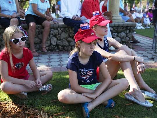 From left, Cora Dousson, 7, of Bonita Springs, Caitlyn Masters, 9, of Estero and Camille Dousson, 10, of Bonita Springs listen to the Memorial Day service at Riverside Park in Bonita Springs on Monday, May 30, 2016. (Dorothy Edwards/Staff)