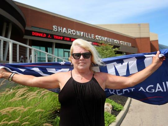 Teresa Willis, of Mason Ohio, holds onto a Donald Trump