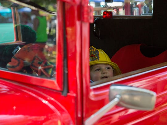 Madeline Hyatt, 2, peaks out the window of a 1931 Chevy pickup that has been converted into a fire truck after September 2001during the Frog Follies car show on Saturday afternoon.