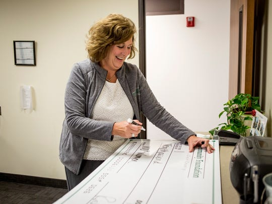 Sue Schmid, development officer at the Community Foundation of St. Clair County, fills out a $10,000 check for Mara McCalmon's non-profit, P.S. You're My Hero,  Friday, September 23, 2016 at the St. Clair County Courthouse.