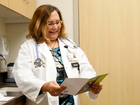 Dr. Nicole Nisly (left) smiles as she reads the card