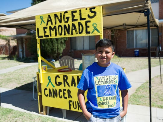 Angel Reyes,9, stands in front of his Lemonade stand, Reyes is using the money he earns  from lemonade sales to help with his grandfathers cancer treatment, Wednesday, March 22, 2017.