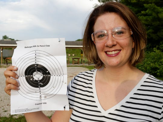 Emily Rendall-Araujo of Glenbeulah holds up her target after shooting at the Coastal Gun Safety Seminar Tuesday July 12 at the Sheboygan Rifle and Pistol Club near Haven.  Rendall-Arauio said she went to the seminar to become more familiar with firearms and to know more about safe operation techniques.